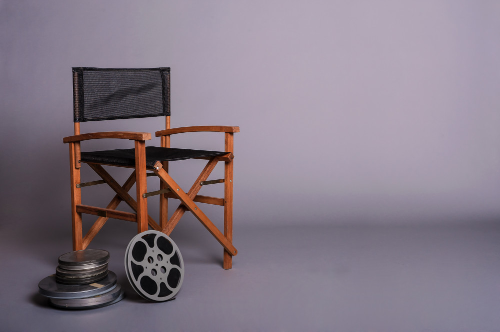Director's cut concept of movie director chair with 16mm film spools