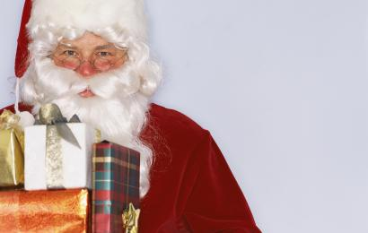 Santa Claus Holding Wrapped Presents --- Image by © Royalty-Free/Corbis